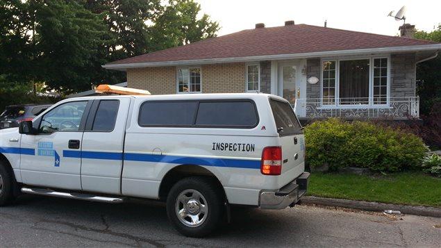 Un véhicule de Revenu Québec devant une maison.