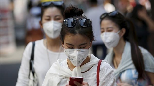 Des passantes munies de masques respiratoires dans les rues de Séoul, en Corée du Sud