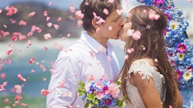 Un couple de jeunes mariés s'embrasse sous un déluge de fleurs.