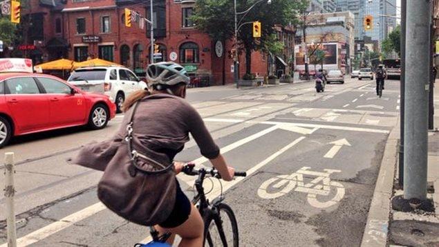 Une cycliste à l'intersection des rues Adelaide et John.