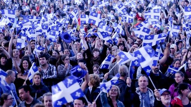 Des gens rassembl�s avec des drapeaux du Qu�bec