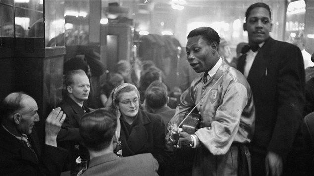 Au bar du rez-de-chaussée du Rockhead's Paradise, le célèbre chanteur calypso, Lord Caresser, visite des tables bondées, 1951.