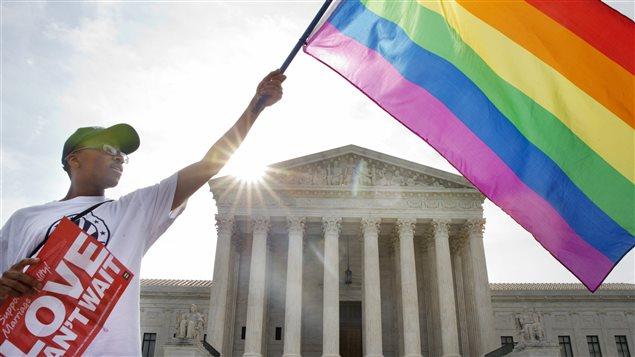 Un homme brandit le drapeau arc-en-ciel de la fierté gaie devant l'édifice de la Cour surprême, à Washington, le 26 juin.