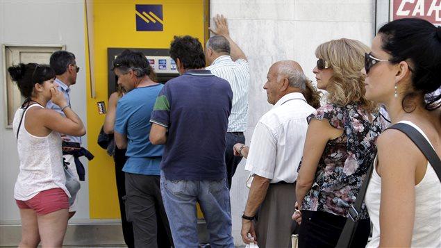 Des personnes font la file pour retirer de l'argent d'un guichet automatique devant une banque de l'île de Crète.