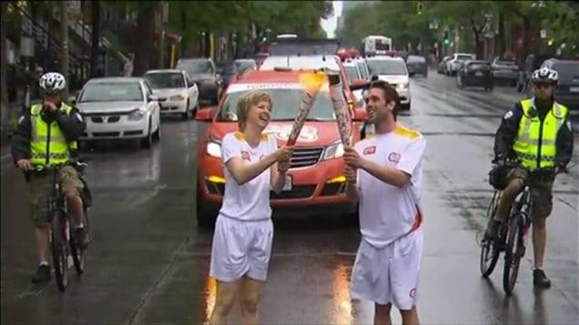 Marie-José Turcotte transmet la flamme des Jeux panaméricains au plongeur Maxim Bouchard.