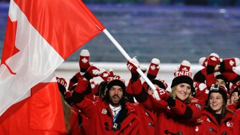 Team Canada proudly waves the Canadian Maple Leaf flag at the Sochi olympics wearing Canada toques voted the most Canadian of clothing items. They also have special Canada mittens and