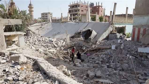 Des résidents inspectent les dégâts des bombardements de jeudi attribués à l'armée syrienne dans la ville de Tafas à Daraa.
