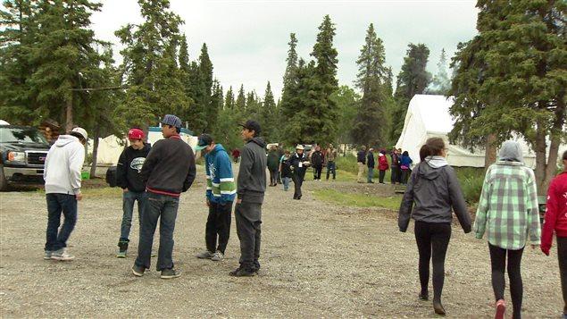 de nombreux jeunes discutent près de grandes tentes