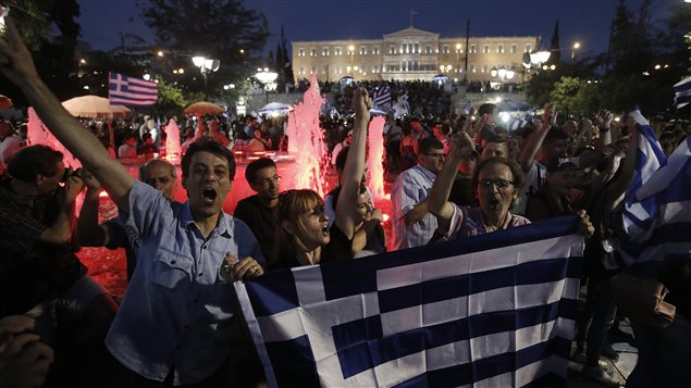 Des Grecs célèbrent la victoire du non au référendum devant le Parlement, place Syntagma, à Athènes.