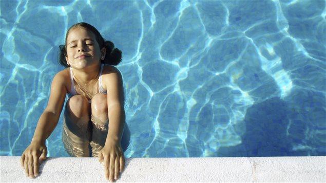 Une jeune fille se baigne dans une piscine