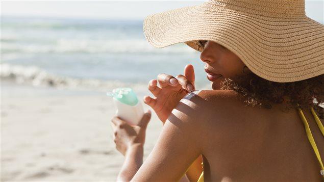 Une femme s'applique de la crème solaire.