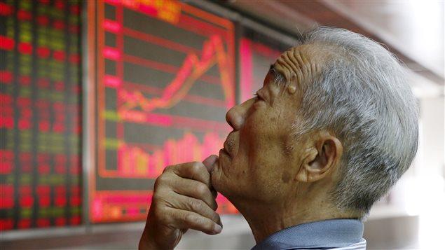 Un investisseur surveille les informations boursières à Pékin.