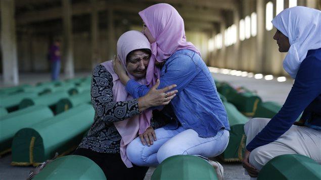 Une femme pleure devant le cercueil de son mari au mémorial des victimes du massacre de Srebrenica, érigé à Potocari.