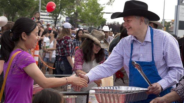 Le premier ministre canadien Stephen Harper sert des crêpes au Stampede de Calgary il y a deux semaines. Quand va-t-il déclencher des élections?