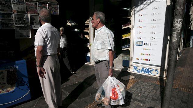 Des citoyens d'Athènes lisent les manchettes des journaux annonçant l'accord survenu entre la Grèce et les leaders de la zone Euro.