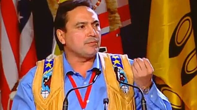 Assembly of First Nations Chief Perry Bellegarde will lead talks with provincial and territorial premiers this week in Newfoundland and Labrador. We see a handsome, dark-haired man wearing a dark blue dress shirt under ceremonial beige, blue and yellow trappings over each shoulder. He is making a point with his right hand and sits in front of First Nations flags.