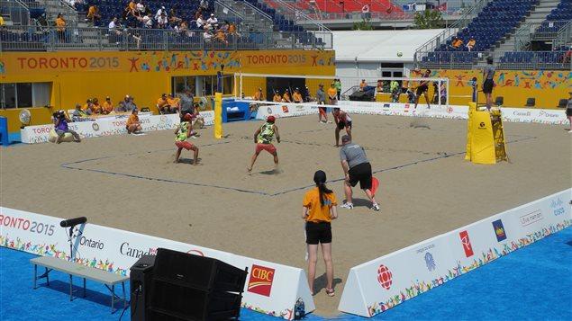 Une bénévole des Panam (en orange) surveille le terrain durant un match de volleyball de plage.