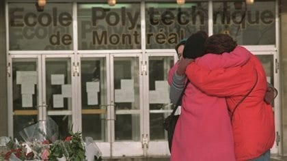 Three women embrace after laying flowers in front of École Polytechnique​ in Montreal, where a gunman killed 14 women on Dec. 6, 1989. All three are standing at the right of the picture. All are wearing red winter coats. In the background is the school building itself. Across its windows is written of École Polytechnique​ de Montreal. In the front of the building to the left, flowers have been laid.