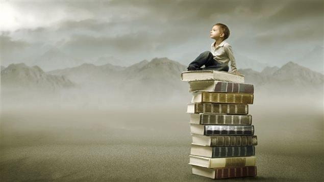 Un petit garçon est assi sur une pile de livres. Derrière lui, une chaîne de montagnes dans le brouillard.