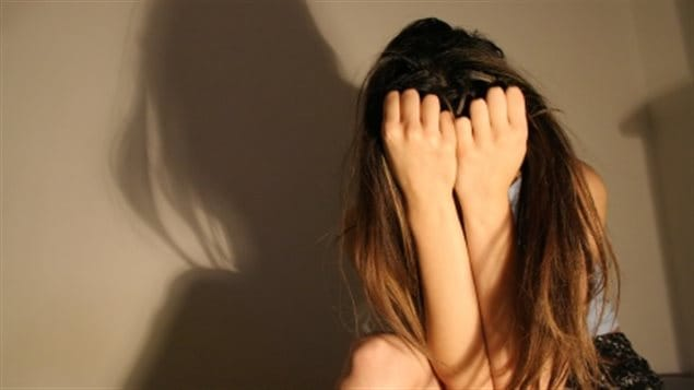 Statistics Canada reports that half of all women in Canada have experienced at least one incident of physical or sexual violence after the age of 16. We see a young fair-haired girl seated with her hands and arms covering up her face. Her large shadow covers much of a grey wall behind her.