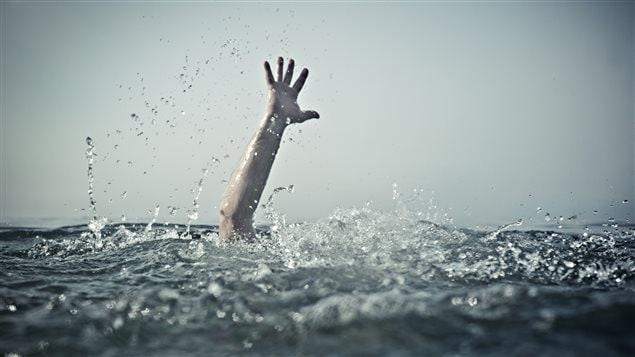 Une main est agitée hors de l'eau.