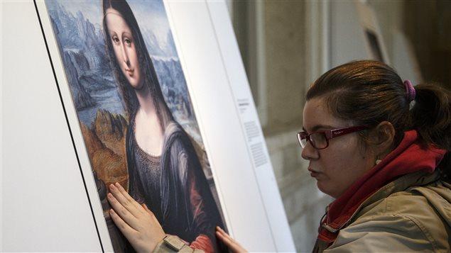 Une personne aveugle découvre une oeuvre d'art.
