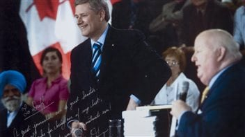A signed hand-out photo shows Prime Minister Stephen Harper with suspended former Conservative Senator Mike Duffy.  The photo is an exhibit in the trial of Duffy on 31 charges related to inappropriate Senate expenses.