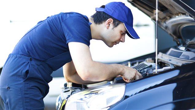 Mécanicien qui effectue une réparation à une automobile.