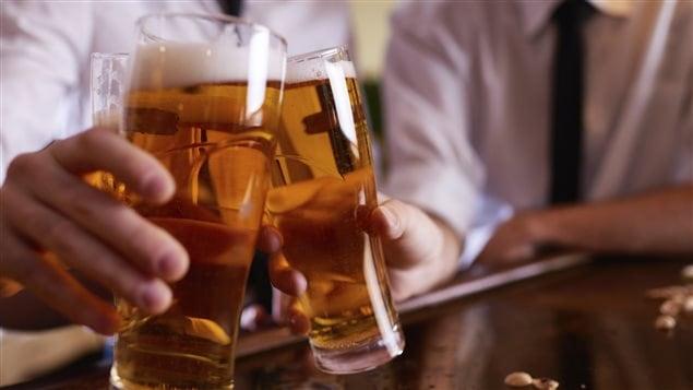 Des amis trinquent, un verre de bière à la main.