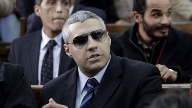 Mohamed Fahmy in a court appearance earlier this year. He is wearing a dark suit and dark tie over a blue shirt. He wears dark glasses under close-cropped salt-and-pepper hair. He is looking to his left.