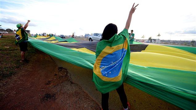 Des activistes du mouvement Brésil libre installent une bannière le long d'une autoroute.