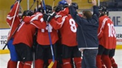 Some things don't change, no matter what the league. Team Quebec celebrates after taking the gold at the 2015 Courage Canada National Blind Hockey Tournament this past spring in Toronto.  We see the Quebec team dressed in red sweaters and blue pants pound and hug each other in a big circle near the end boards.