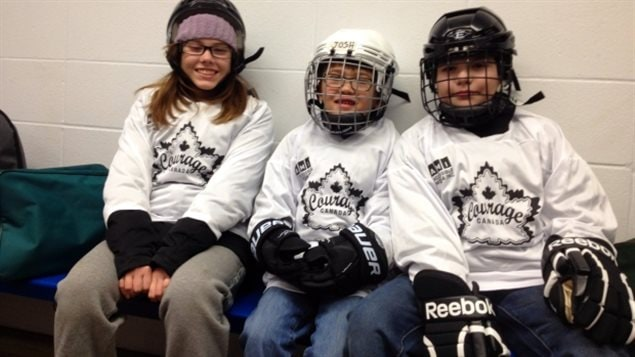 """Kids at a Courage Canada hockey camp. They, too, now have a higher league to shoot for. We see three kids dressed in their white hockey seaters with a Courage Canada logo (a maple leaf and the words """"Courage Canada). We have a tall girl with shoulder-length brown hair to the left. She is not wearing a mask. In the middle we have a short boy with a white birdcage helmet on.On the right a taller boy. He wears a dark birdcage helmet. The girl has a big smile. The boys are a bit more serious. This is hockey, after all."""