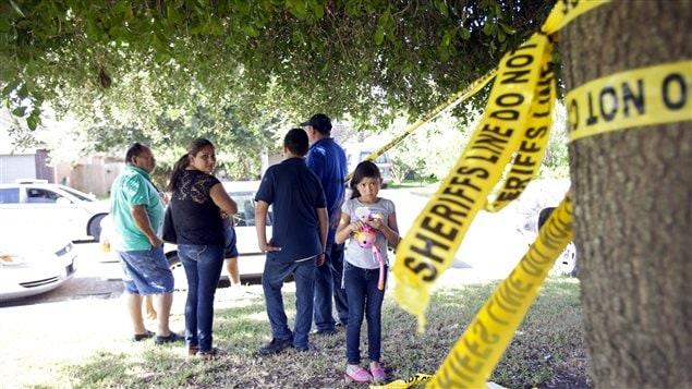 Des voisins devant la maison au Texas où deux adultes et six enfants ont été retrouvés morts