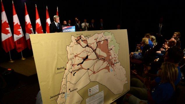 Stephen Harper montrant une carte des zones contrôlées par les terroristes en Syrie et en Irak qui seraient donc probablement parmi les endroits où il interdirait les Canadiens à voyager s'il est réélu. (Sean Kilpatrick / Presse canadienne)