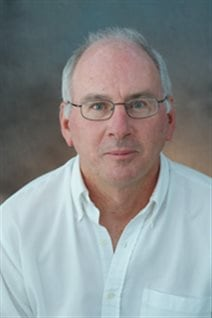Professor Paul Hebert has set himself a giant task: to get the DNA barcode of all the world's species. We see him in a posed photo in a white dress shirt with the collar open. He wears glasses and his grey hair is receding. He has a look of determination on his face.