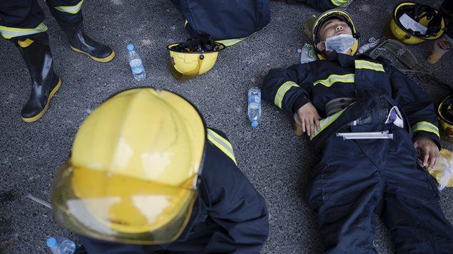 Bomberos en un momento de descanso mientras combatían el incendio en Tianjin. Por lo menos 12 de ellos murieron en las dos explosiones.