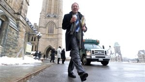 Conservatives are hoping that Irwin Cotler's exit from politics will open the door for them in Mount Royal. We see Cotler dressed in a blue overcoat and grey suit on a winter's day on Parliament Hill. He holds a coffee in his right hand and a newspaper in the other hand. It's a full-length shot, something resembling a vacation photo.