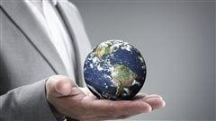 Un homme en complet d'affaires tient le monde dans la paume de sa main.