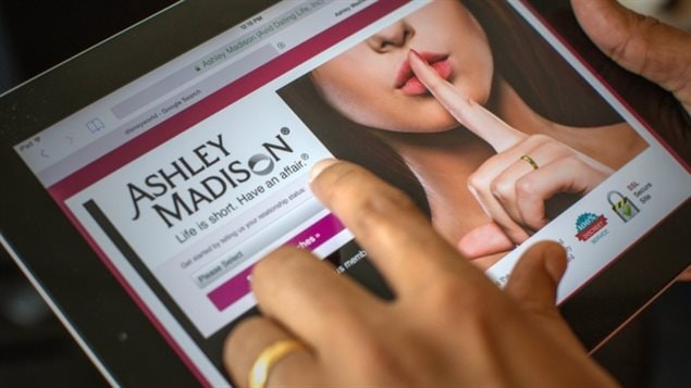 The investigation in Ashley Madison could affect the lives of 37 million people. We see a tablet being held by a left hand that has a wedding rind on its ring finder. On the tablet, we see the Ashley Madison website, which shows the face of a woman from the bottom of the nose down. She holds her left index finger up to her lips, the traditional signal to remain quiet.