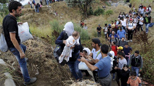 Des migrants traversant la frontière entre la Grèce et la Macédoine.