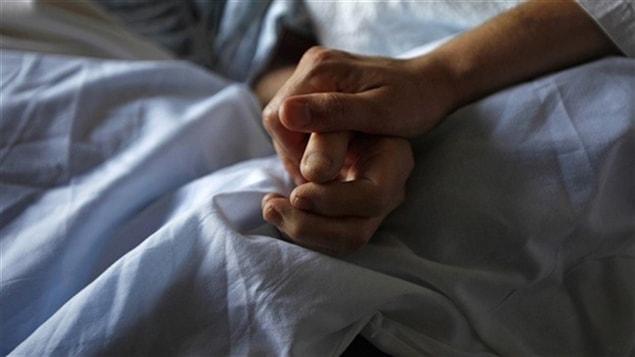 Une main qui tient la main d'un mourant