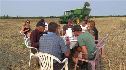 Ronald Vermette et sa famille prennent une pause repas en pleine récolte près d'Aubigny, dans le sud du Manitoba.