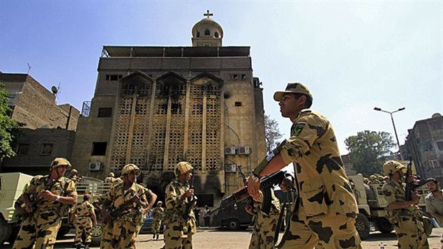 May 2011: Egyptian Army soldiers stand guard outside the Virgin Mary Coptic Christian church in the Imbaba neighbourhood of Cairo, Egypt. The church was burned by a Muslim mob