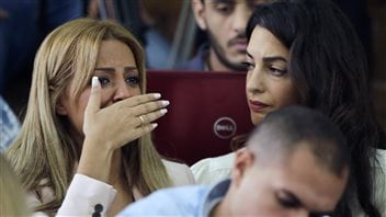 In this Aug. 29, 2015 file photo, the wife of Mohammed Fahmy bursts into tears upon hearing the verdict against her husband. Lawyer Amal Clooney looks on.