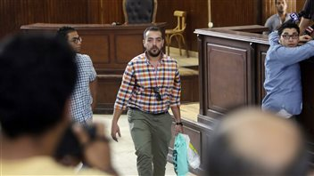 Egyptian journalist Baher Mohammed carried a bag of clothes in the Cairo courtroom prior to his conviction and imprisonment.
