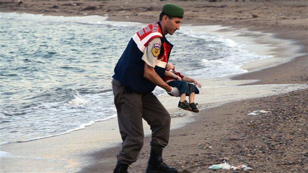Dans la ville de Bodrum en Turquie, un policier tient dans ses bras un jeune migrant noyé qui tentait avec sa famille de se rendre sur l'île grecque de Kos.