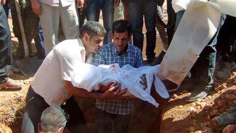 Le père du petit réfugié kurde Alan Kurdi enterre son fils dans sa ville natale de Kobané, en Syrie.