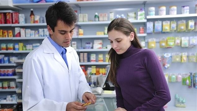 Un pharmacien conseille une cliente sur sa prescription.