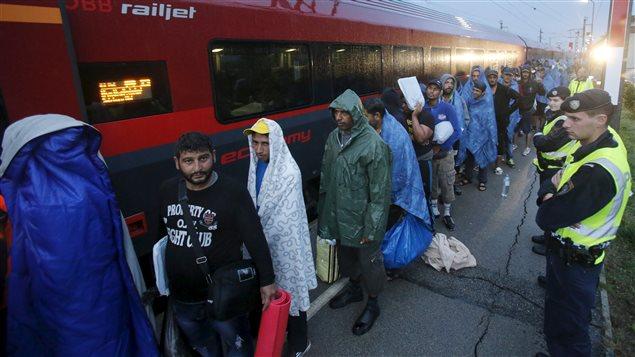 Des migrants attendent pour prendre le train vers l'Allemagne, à partir de l'Autriche